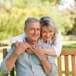 Senior woman hugging her husband who is on the bench — Stock Photo #10850163