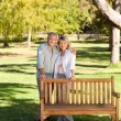 Portrait of a lovely couple behind the bench — Stock Photo