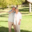 Elderly couple taking a photo of themselves in the park — Stock Photo
