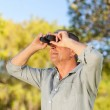 Senior man looking at the sky with his binoculars — Stock Photo #10850293