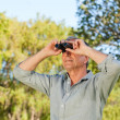 Senior mlooking at sky with his binoculars — Stock Photo #10850298