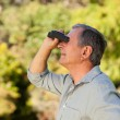 Senior man looking at the sky with his binoculars — Stock Photo