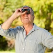 Elderly man looking at the sky with his binoculars — Stock Photo