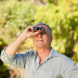 Elderly mlooking at sky with his binoculars — Stock Photo #10850330