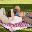 Woman reading while her husband is sleeping in the park — Stock Photo #10850416