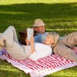 Woman reading while her husband is sleeping in the park — Stock Photo #10850419