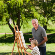 Grandfather and his grandson painting in the garden — Stock Photo