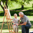 Stock Photo: Grandfather and his grandson painting in the garden