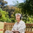 Stock Photo: Elderly womlistening to some music