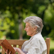 Reired woman reading a book on the bench — Stock Photo