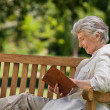 Reired woman reading a book on the bench — Stock Photo #10850611