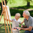 Grandfather and his grandson painting in the garden — Stock Photo #10850626