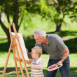 Stock Photo: Grandfather and his grandson painting in garden