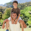Man giving son a piggyback — Stockfoto