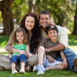 Happy family sitting in the garden — Stockfoto