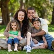 Happy family sitting in the garden — Stock Photo #10850747