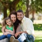 strålande familj sitter i trädgården — Stockfoto #10850766