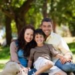 glada familjen sitter i trädgården — Stockfoto #10850787