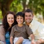 radosny rodzina siedzi w ogrodzie — Zdjęcie stockowe