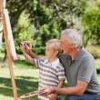 Happy Grandfather and his grandson painting in the garden — Stock Photo #10850986