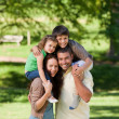 Parents giving children a piggyback - Stockfoto
