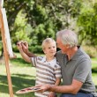 Happy Grandfather and his grandson painting in the garden — Stock Photo