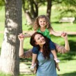 Stock Photo: Mother giving daughter piggyback