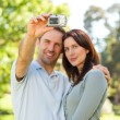 Couple taking a photo of themselves in the park — Stock Photo
