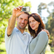 Stock Photo: Couple taking a photo of themselves in the park