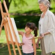 Grandmother and her granddaughter painting in garden — Stock Photo #10851298