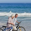 Retired couple with their bikes on the beach — Stock Photo #10851527