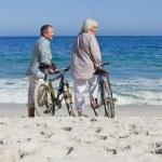 Senior couple with their bikes on the beach — Stock Photo