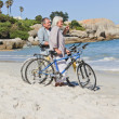 Senior couple with their bikes on the beach — Stock Photo