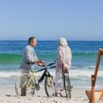 Elderly couple with their bikes on the beach — Stock Photo