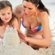 Daughter with her mother making a sand castle - Stok fotoğraf