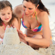 Daughter with her mother making a sand castle - 