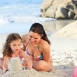 Daughter with her mother making a sand castle — Stock Photo #10852070