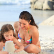 Daughter with her mother making a sand castle — Stock Photo #10852073