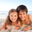 Little boy and his sister lying down on the beach — Stock Photo