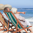 Retired couple sitting on deck chairs — Stock Photo #10852133