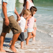 Stock Photo: Family walking on the beach