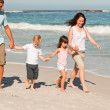 Family walking on the beach — Stock Photo