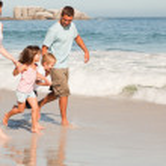 Family running on the beach — Stock Photo