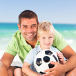 Happy father playing football with his son - Stock Photo