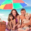 Family picnicking under a sol umbrella on the beach — Stock Photo