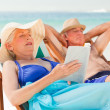 Woman reading a book while her husband is sleeping at the beach — Stock Photo #10852954
