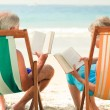 Stock Photo: Couple reading at the beach