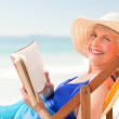 Elderly woman reading a book at the beach — Stock Photo