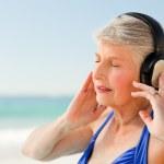 Senior woman listening to music at the beach — Stock Photo #10853081