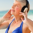 Senior woman listening to music at the beach — Stock Photo